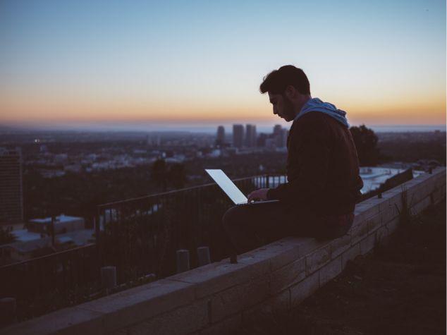 屋上でパソコンを使う男