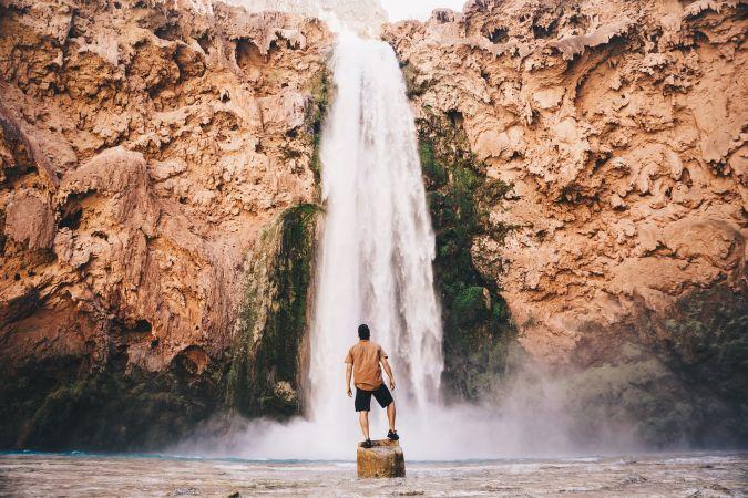 滝の前で佇む男