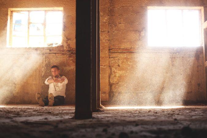 廃墟で酒を飲む男
