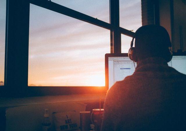 夕焼けの中パソコンを操作する男