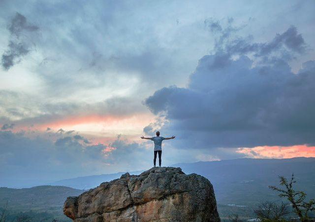 岩の上で両手を広げる男