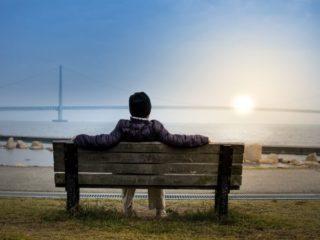 ベンチに座って海を見る人