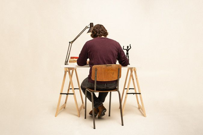 机に向かって作業する男