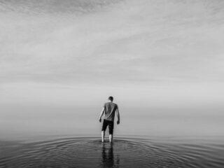 曇りの湖に佇む男